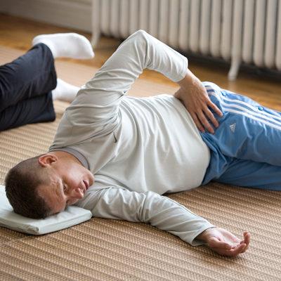 The Feldenkrais Method - man on the floor for Aches and Pains